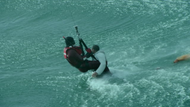 cu aerial shot of paramedic rescuing man from sea / cape town, western cape, south africa - retter rettungsaktion stock-videos und b-roll-filmmaterial