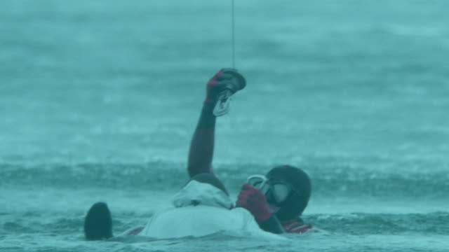 cu aerial shot of paramedic rescuing man in sea / cape town, western cape, south africa - 救助隊点の映像素材/bロール