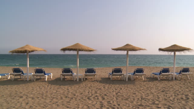 WS Shot of parasols with lounge chair on beach / Marbella, Andalusia, Spain