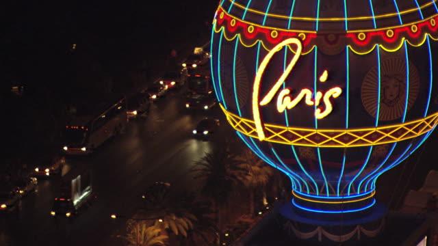 vídeos y material grabado en eventos de stock de cu aerial td shot of paris neon sign and car traffic on street at night / las vegas, nevada, united states - paris las vegas