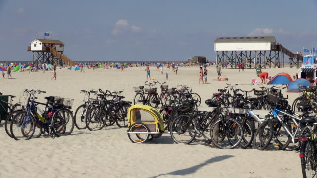 ws shot of parked bicycle and peoples playing on beach near cafe, north sea north frisia, / st. peter ording, schleswig holstein, germany - nordfriesische inseln stock-videos und b-roll-filmmaterial