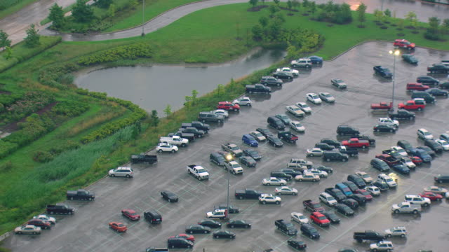 ms aerial zo shot of parking lot outside factory during overcast and rainy day / dearborn, michigan, united states - dearborn michigan stock videos and b-roll footage