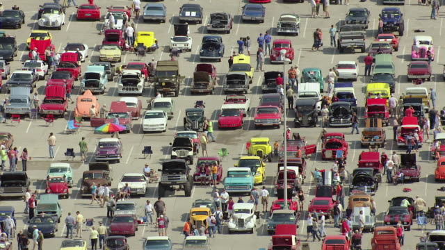 ms aerial shot of parking lot with people admiring cars at blue suede cruise car show / tupelo, mississippi, united states - motor show stock videos and b-roll footage