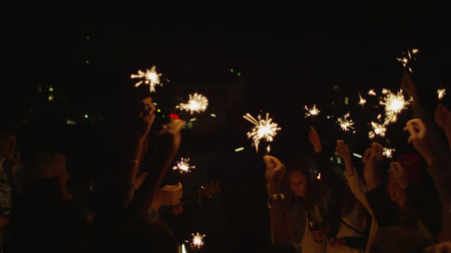 """MS PAN Shot of Party with group of young people and band on rooftop, lighting and holding sparklers, dancing, playing music / Berlin, Germany"""