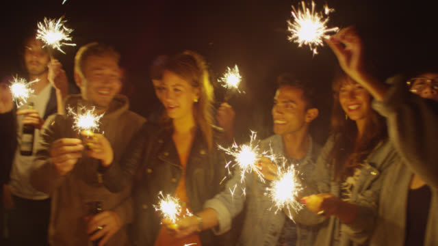 """MS PAN ZI Shot of Party with group of young people on rooftop, holding sparklers and smiling / Berlin, Germany"""