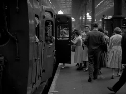 shot of passengers walking along a platform and onto a waiting passenger train at victoria station 1958 - järnvägsvagn tåg bildbanksvideor och videomaterial från bakom kulisserna