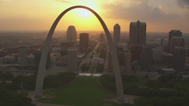 MS AERIAL Shot of passing Gateway Arch and western view of downtown during sunset / St Louis, Missouri, United States