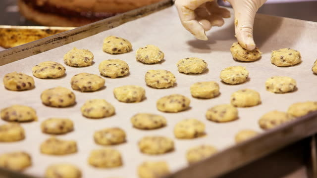 cu shot of pastry chef putting chocolate chip cookie dough in baking pan / rome, lazio, italy - chocolate chip stock videos & royalty-free footage
