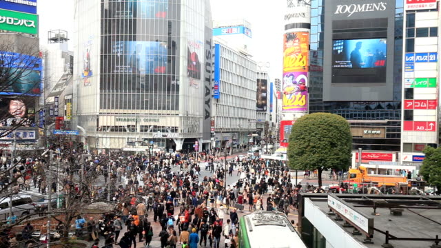 ms pan shot of pedestrians and cars crossing at shibuya crossing / shibuya ku, tokyo, japan - 広告点の映像素材/bロール