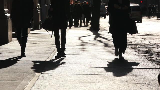 ms shot of pedestrians and dog walking down shining sidewalk at soho / new york, united states - human limb stock videos & royalty-free footage