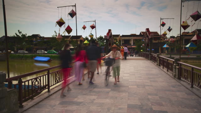 ms t/l shot of pedestrians and scooters busily cross bridge over browny/green river with residential buildings on other side and decorations hang in breeze / hoi an, vietnam - river green stock videos & royalty-free footage
