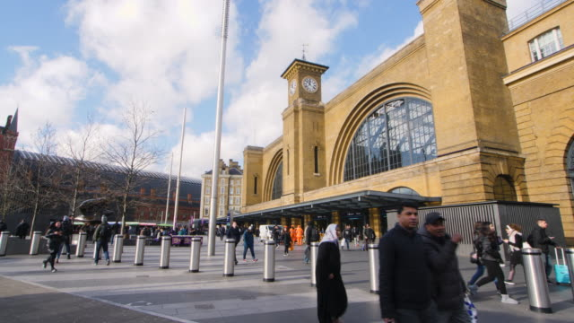 Shot of pedestrians walking past the front exterior of Kings Cross Station, London.