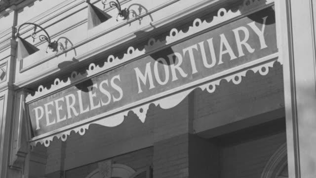 ms shot of peerless mortuary sign - pompe funebri video stock e b–roll