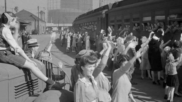 ms shot of people at train station waving to departing soldiers and marching band leads parade of soldiers who have returned - waving stock videos & royalty-free footage