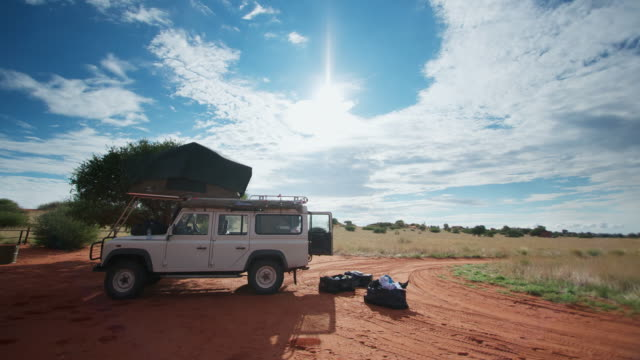 ms t/l shot of people busy packing up camp equipment to stow in all terrain vehicle under streaming cloudscape, over blue sky / kalahari, windhoek, namibia - packing stock videos & royalty-free footage