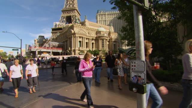 ms shot of people crossing road in city / las vegars, united states - las vegas crosses stock-videos und b-roll-filmmaterial