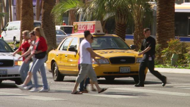 cu shot of people crossing road in city / las vegars, united states - las vegas crosses stock-videos und b-roll-filmmaterial