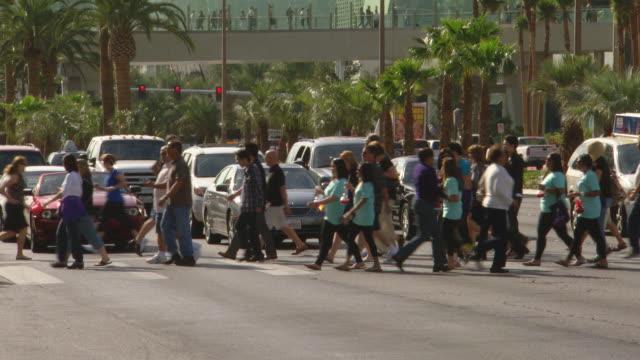 ms shot of people crossing road / las vegars, united states - las vegas crosses stock-videos und b-roll-filmmaterial