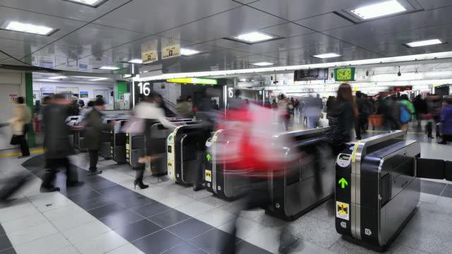 ms t/l shot of people crowd passing through jr train station ticket system / tokyo, japan - 自動改札機点の映像素材/bロール