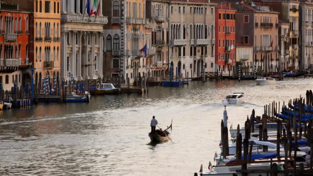 WS Shot of people enjoying there journey and several gondolas on harbor at sunset / Venice, Veneto, Italy