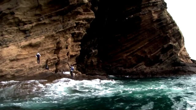 Shot of people fishing under cliff at Jeju Island