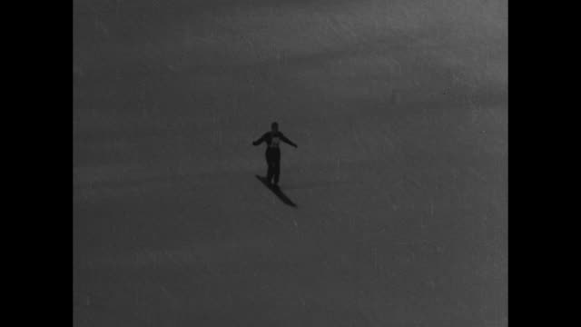 shot of people gathered to watch ski jumping / man goes off ski jump / he sails past camera and lands / after landing man continues skiing down slope... - ski jumping stock videos and b-roll footage