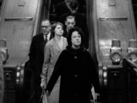 """vídeos de stock e filmes b-roll de shot of people getting off """"down"""" escalator at piccadilly circus station; 1963. - enfeites para a cabeça"""