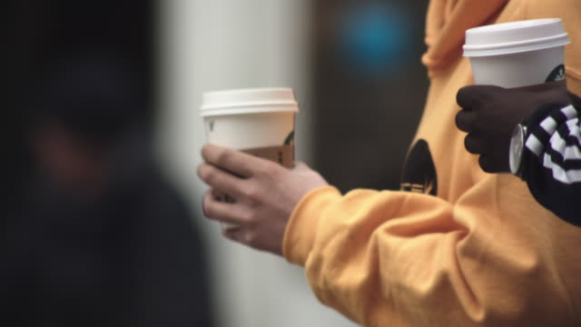 CU TS SLO MO Shot of people holding coffees in city / United Kingdom