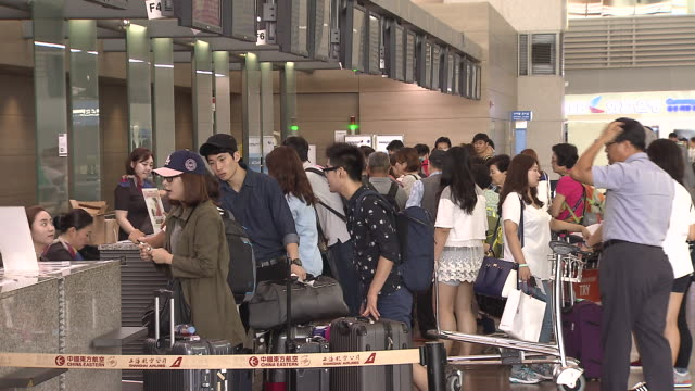 Shot of people in a row at the check-in counter of Incheon International Airport