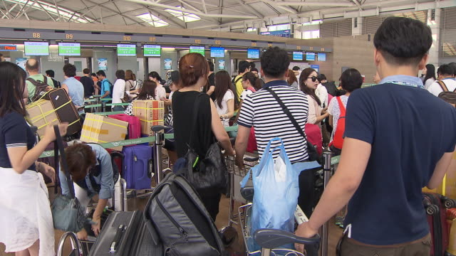 vidéos et rushes de shot of people in a row at the check-in counter of incheon international airport - file attente
