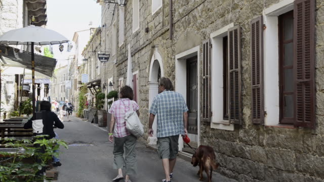 MS Shot of People in old town alley / Porto Vecchio , Corsica, France
