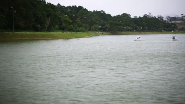 stockvideo's en b-roll-footage met ms t/l shot of people in pedal boats on lake / dalat, vietnam - waterfiets