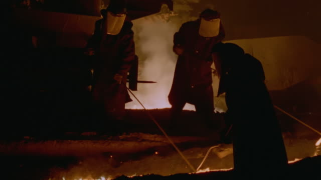 MS PAN Shot of People in protective clothing tending to blast furnace