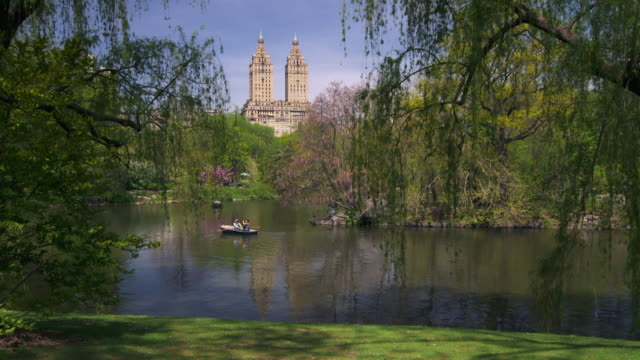 shot of people in rowboats on the lake in central park, manhattan on a sunny day.  the towers of the san remo apartments can be seen in the skyline - remo stock videos and b-roll footage