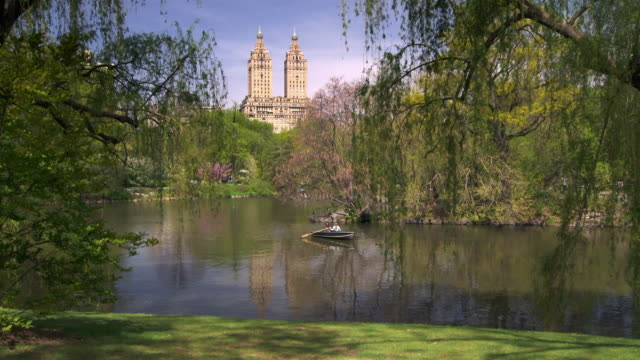vidéos et rushes de shot of people in rowboats on the lake in central park, manhattan on a sunny day.  the towers of the san remo apartments can be seen in the skyline - central park manhattan