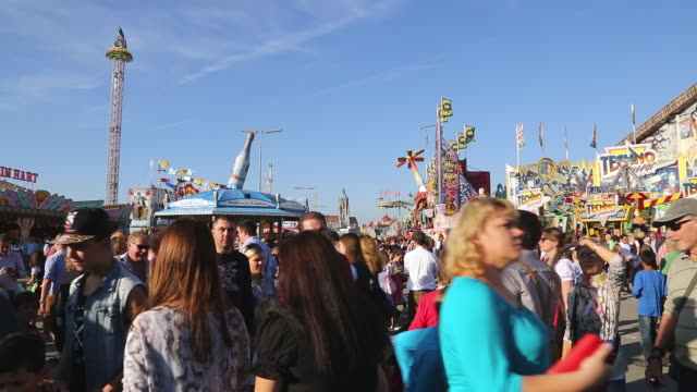 ws shot of people in traditional dresses at oktoberfest during sunny day with rides and beer tents in background / munich, bavaria, germany - oktoberfest stock videos & royalty-free footage