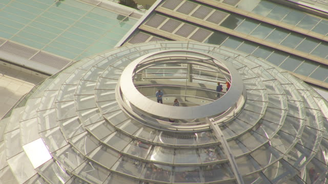 ms aerial pan shot of people inside dome of reichstag building / berlin, germany - cupola video stock e b–roll