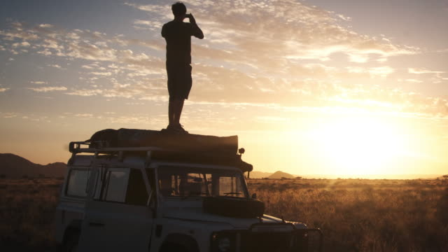 ms t/l shot of people looking out over savannah from roof of all terrain vehicle as sun goes down / naukluft, windhoek, namibia - 四輪駆動車点の映像素材/bロール