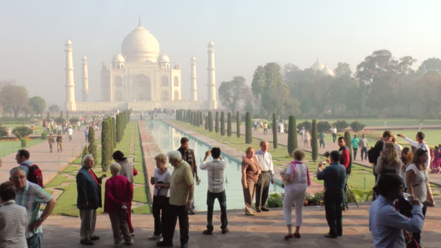 ms shot of people mill about walk way in front of reflecting pool of taj mahal / agra, uttar pradesh, india - agra stock videos and b-roll footage