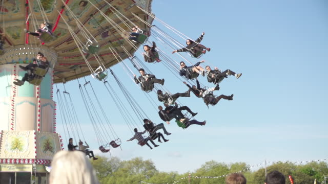 MS LA SLO MO Shot of People on festival carousel in sky / Victoria Park, London, United Kingdom