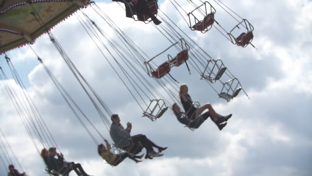 MS SLO MO Shot of People on festival ride carousel in sky / Victoria Park, London, United Kingdom