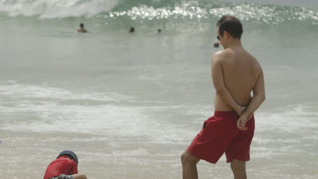 ms shot of people on the beach / rio, brazil - stare in piedi video stock e b–roll