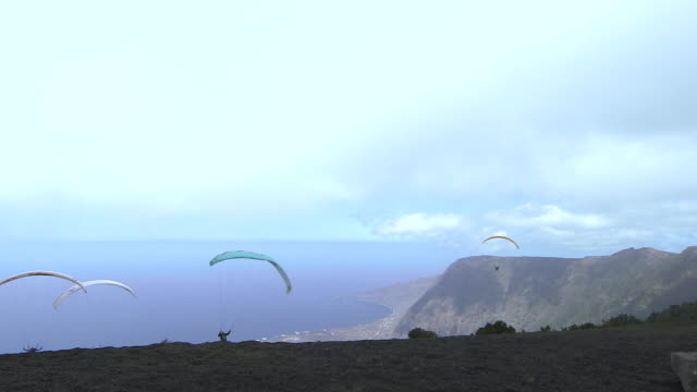 vídeos de stock e filmes b-roll de shot of people paragliding off a mountain on the island of el hierro. - ilha