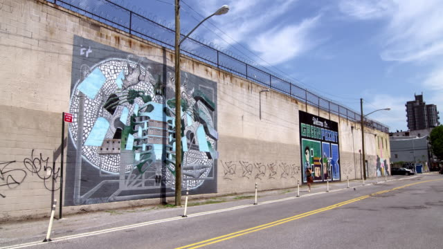 shot of people passing by graffiti art on a wall in greenpoint, brooklyn on a sunny day - graffiti stock videos & royalty-free footage