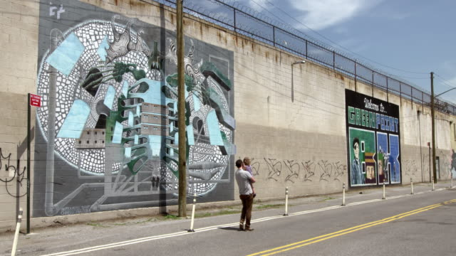 shot of people passing by graffiti art on a wall in greenpoint, brooklyn on a sunny day - greenpoint brooklyn stock videos & royalty-free footage