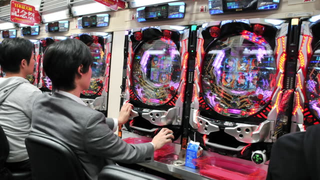 MS T/L POV Shot of people playing Pachinko machines / Tokyo, Japan