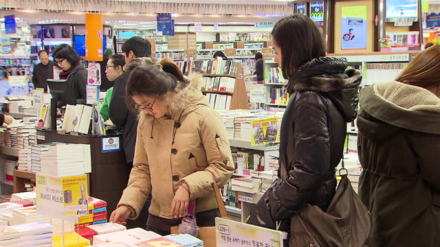 ms shot of people reading book at kyobo book store / seoul, seoul, south korea - 書店点の映像素材/bロール