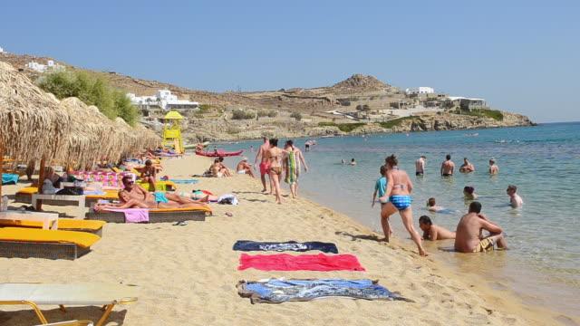 vídeos de stock, filmes e b-roll de ms shot of people relaxing and walking on paradise beach / mykonos, greece - toalha de praia