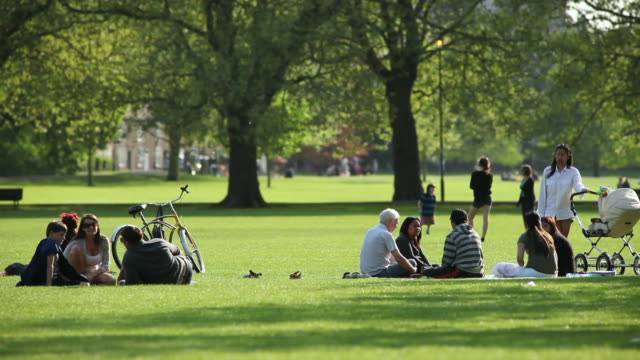 MS Shot of People relaxing on Jesus Green park / Cambridge, Cambridgeshire, United Kingdom