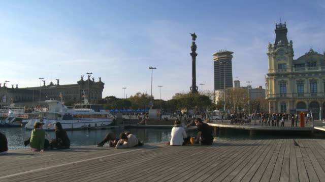 WS Shot of people relaxing on Mare magnum bridge with sea gulls flying in air / Barcelona, Catalonia, Spain